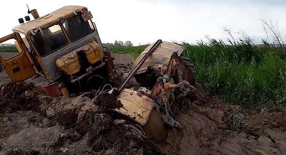Кировец в грязи по самую раму